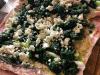Spinat und Feta verteilt auf dem aufgeklappten Schweinerollbraten
